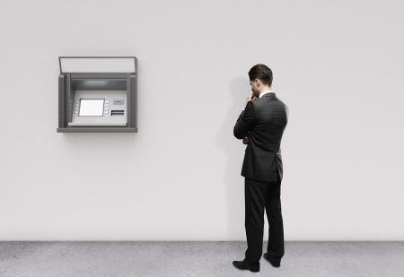 man thinking and looking at atm