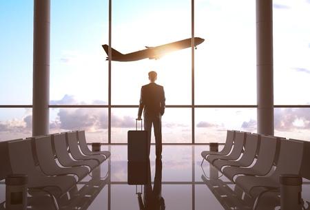 Foto de businessman in airport and airplane in sky - Imagen libre de derechos