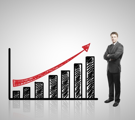 Photo for young businessman standing and drawing arrow graph - Royalty Free Image