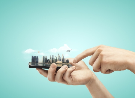 hand holding mobile phone with model city