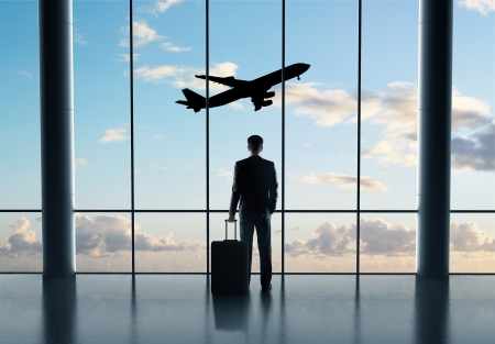 man in airport with luggage and looking in airplane