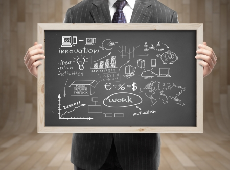 businessman in suit holding blackboard with business strategy in office
