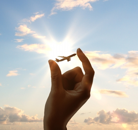 Foto de hand holding airplane on sky background - Imagen libre de derechos