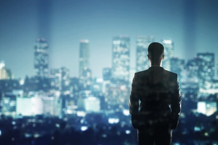 businessman in suit looking to night cityの写真素材