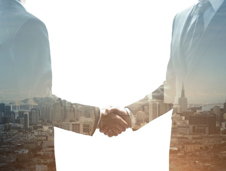 two businessmen shaking hands on city backgroundの写真素材