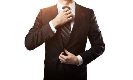 businessman adjusts his tie on white background