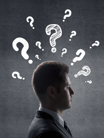 man with questions symbol on gray wall background