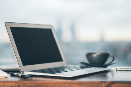 Blurry laptop, black coffee cup and other items on wooden table