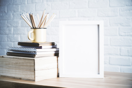 Photo pour Desk with blank picture frame and pencils in iron mug placed on books and wooden box. Mock up - image libre de droit