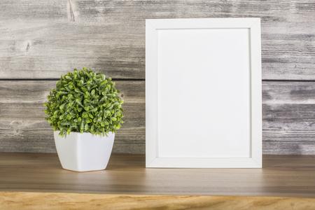 Photo pour Blank white frame and plant on wooden surface - image libre de droit
