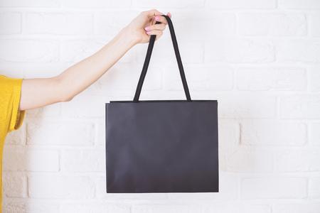 Photo pour Closeup of female hand holding black shopping bag on white brick background. - image libre de droit