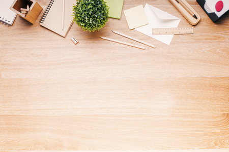 Photo pour Topview of wooden desk with office tools and plant. Mock up - image libre de droit