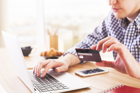 Photo pour Online shopping and payment concept with male at desk typing on computer keyboard and holding a credit card - image libre de droit