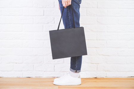 Photo pour Sideview of female legs with blank shopping bag on white brick wall. Mock up - image libre de droit