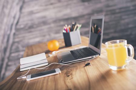 Foto de Side view of designer desk with laptop, smartphone, office tools and orange - Imagen libre de derechos