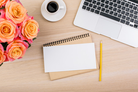 Photo for Top view of creative workplace with beautiful flowers, laptop keyboard, coffee cup and blank paper. Mock up - Royalty Free Image