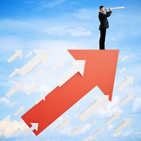 Photo pour Success concept with businessman on red arrow looking into the distance on sky background - image libre de droit
