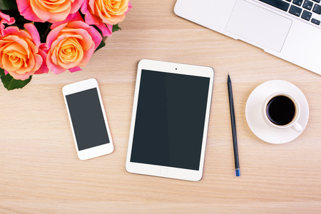 Photo for Top view of creative woman's desktop with roses, blank smart phone and tablet screens, coffee cup, pencil and laptop keyboard. Mock up - Royalty Free Image