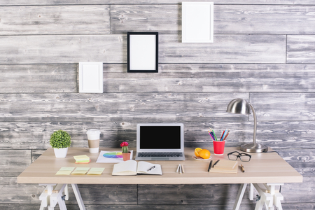 Photo pour Modern designer workplace with blank laptop, picture frames above, plants, stationery and other items. Mock up - image libre de droit