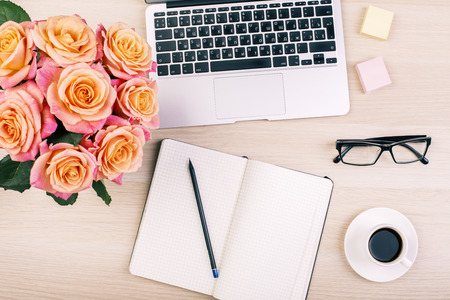 Photo pour Top view of creative  woman's desktop with open notepad, pencil, glasses, coffee cup, roses and laptop keyboard - image libre de droit