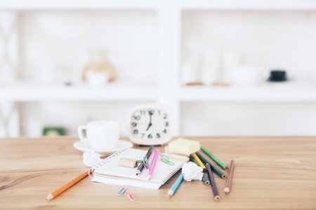 Messy office desktop with stationery items, clock and coffee cup with blurry shelves in the background