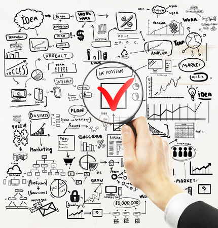 Businessman hand holding magnifier over red checkmark with business drawings around on light background. Nothing is impossible concept