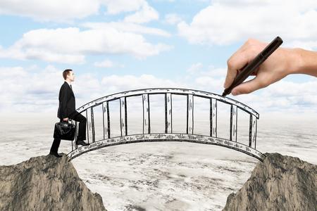 Photo pour Success concept with hand drawing bridge over gap between two cliffs and businessman walking across it on landscape background - image libre de droit