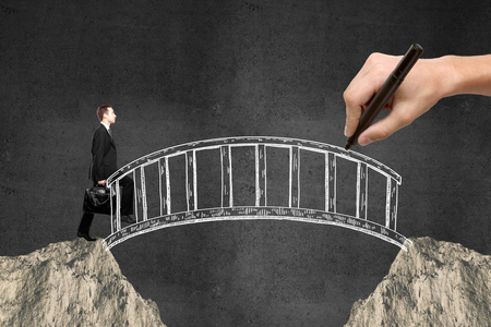 Foto de Success concept with hand drawing bridge over gap between two cliffs and businessman walking across it on dark concrete background - Imagen libre de derechos