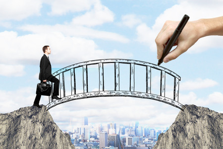 Foto de Success concept with hand drawing bridge over gap between two cliffs and businessman walking across it on city background - Imagen libre de derechos