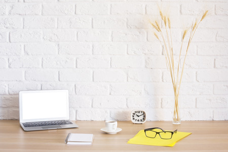 Photo for Bright workplace with blank white laptop, notepad, coffee cup, clock, glasses on yellow paper sheet and wheat spikes on brick wall background. Mock up - Royalty Free Image