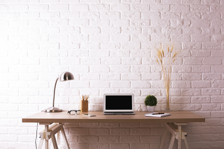 Photo for Front view of creative wooden designer workplace with blank laptop, decorative plants, table lamp, glasses and stationery items on white brick wall background. Mock up - Royalty Free Image