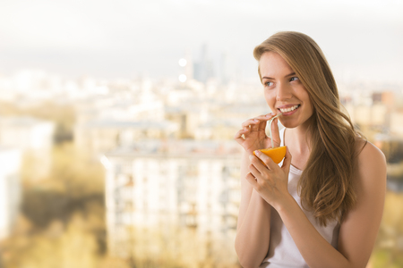 Photo for Pretty woman using straw to drink juice from orange half on blurry city background - Royalty Free Image