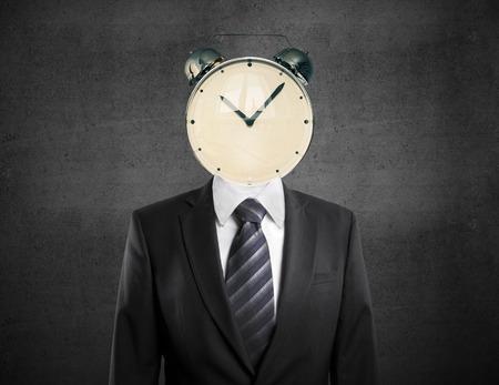 Photo pour Time management concept with alarm clock headed businessman on concrete background - image libre de droit