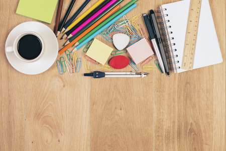 Photo for Top view of messy wooden desktop with coffee cup and colorful stationery items. Mock up - Royalty Free Image