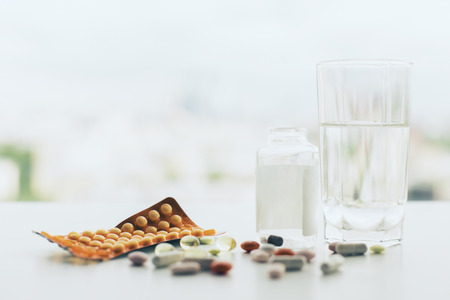 Photo for Closeup of white tabletop with different pills, glass of water, medicine bottle and package - Royalty Free Image