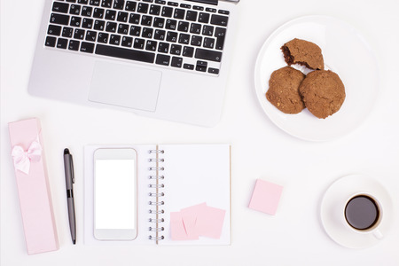 Photo pour Top view of light girly office desktop with blank white smart phone, laptop keyboard, coffee cup, gift case, cookies on plate and other items. Mock up - image libre de droit