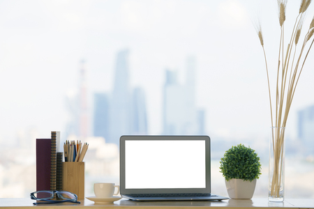 Foto de Closeup of creative designer workplace with blank white laptop computer, decorative plants, stationery items, book, glasses and coffee cup on blurry city background. Mock up - Imagen libre de derechos