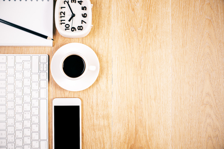 Photo pour Top view of wooden desktop with blank smart phone, keyboard, coffee cup, clock and other items. Mock up - image libre de droit
