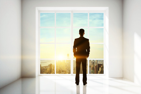 Photo for Businessman looking out of window in bright interior with city view and sunlight. Research concept - Royalty Free Image