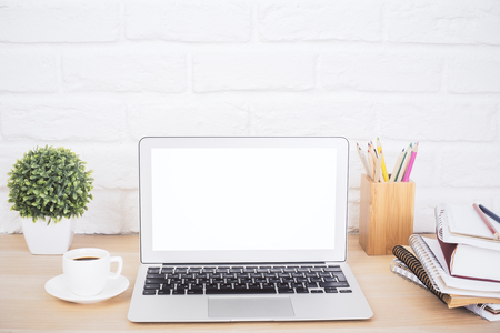 Photo pour Closeup of creative hipster desktop with blank white laptop, coffee cup and other stationery and decorative items on brick background. Mock up - image libre de droit