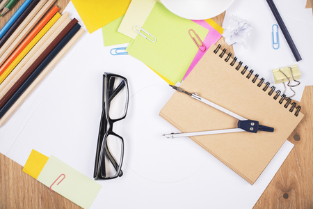 Closeup of wooden office desktop with glasses, colorful pencils, pair of compasses and other stationery items