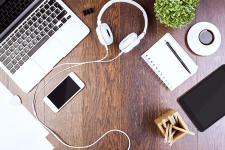 Photo pour Top view of wooden desktop with tablet, laptop, smartphone, headphones, decorative plant and supplies. Mock up - image libre de droit