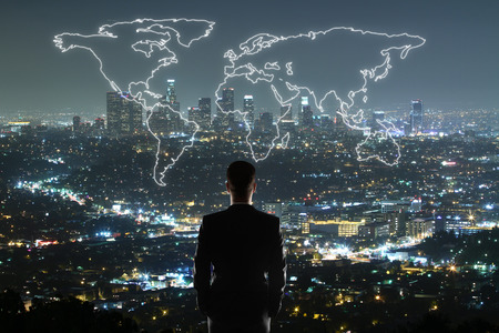Travel concept with businessman looking at anstract map on illuminated night city background