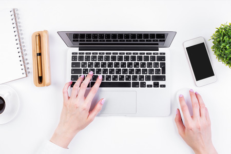 Foto de Top view of girl's hands typing on laptop keypad placed on white office desktop with blank smartphone, coffee cup, decorative plant and supplies. Mock up - Imagen libre de derechos