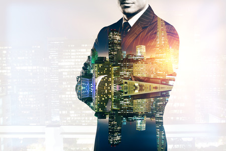 Young man in suit and with folded arms on abstract illuminated night city background. Double exposure