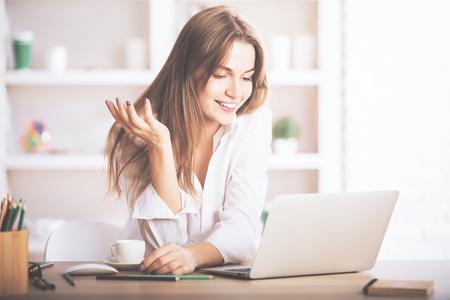 Foto de Portrait of gorgeous, smiling young female using laptop computer at workplace - Imagen libre de derechos