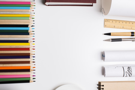 Photo pour Top view of white tabletop with a row of colorful pencils and other stationery items. Mock up - image libre de droit