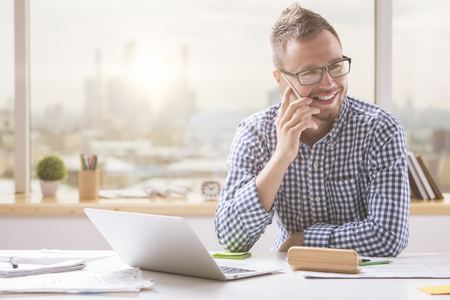 Photo for Portrait of handsome young man in glasses sitting at office desk with laptop computer and talking on mobile phone. Communication concept - Royalty Free Image