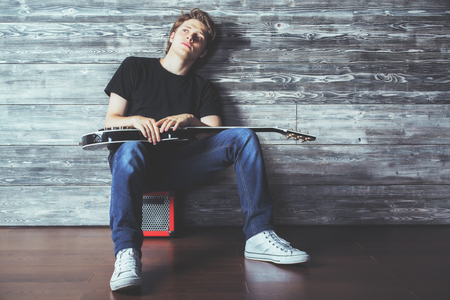 Handsome young man with electric guitar sitting on amplifier in wooden room. Music, concert rehearsal concept