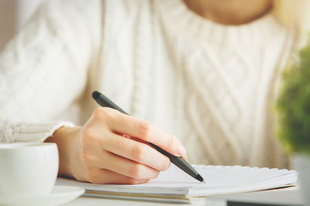 Photo pour Girl writing in spiral notepad placed on bright desktop with coffee cup. Education concept - image libre de droit